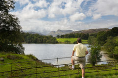 Hiker overlooks Loughrigg Tarn in Lake District. Sun illuminating Langdale Pikes with Loughrigg Tarn in foreground and hiker Royalty Free Stock Photography