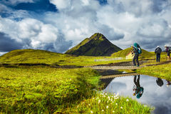Hiker passes through creek, trekking in Iceland Royalty Free Stock Photography