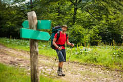 Hiker is passing by signpost Royalty Free Stock Photos