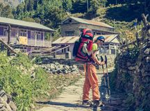 Hiker passing a village. Stock Images