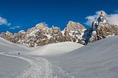 An hiker on a path on the snow heading the Pale of San Martino mountains, Dolomites, italy Stock Photo