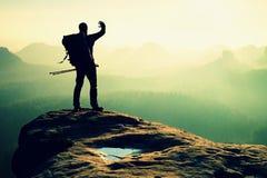 Hiker on peak. Backpacker with poles in hand shadowing eyes, spring daybreak Stock Image