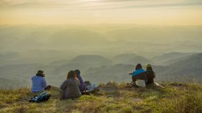 Hiker people take a rest and sit on mountain peak.with autumn mo. Untain fog valley. Bright morning sun shining in sky Stock Photography