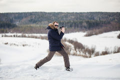 Hiker photographer enjoys a fine winter forest panorama at sunny day Stock Photo