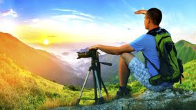 Hiker photographer sitting on a rock looking forward on sunrise. In mountains with a camera on a tripod Royalty Free Stock Photo