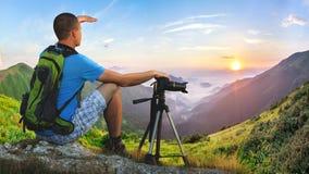 Hiker photographer sitting on a rock looking forward on sunrise Stock Photo
