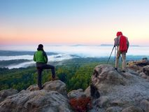 Hiker and photographer stay with tripod on cliff and takes photos. Autumn windy landscape, Royalty Free Stock Photos