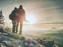 Two people stay at  tripod on background of a mountain range. Hiker and photographer stay with tripod on cliff and takes photos. Two people stay at  tripod on stock photography