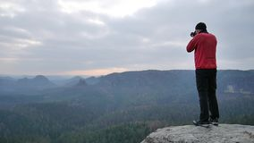 Hiker in pink sportswear   on rocky view point and taking photos of misty morning landscape. Hike in rocks. stock footage