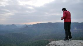 Hiker in pink sportswear   on rocky view point and taking photos of misty morning landscape. Hike in rocks. stock video