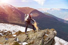 Hiker playing with accompanying Dog staying at rocky Mountains Cliff Royalty Free Stock Images