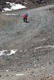 Hiker with poles walking the stony trail Royalty Free Stock Images