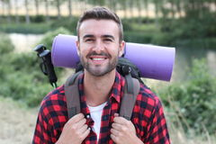 Hiker portrait. Male hiking man happy and smiling during hike trek. Beautiful young sporty model joyful Stock Image