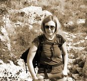 Hiker portrait on the rocky mountain. Elegant woman hiker standing on dangerous rocky terrain Royalty Free Stock Photos