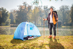 Hiker posing by a pond next to a blue tent Stock Photo