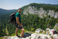 Hiker posing on a very high cliff Stock Photography