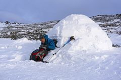 Hiker pours himself a tea from a thermos, sitting in a snowy hut igloo. Against a background of a winter mountain landscape stock images