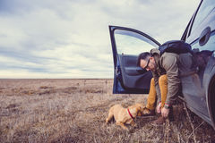 Hiker preparing footwear. Hiker sitting in the car and preparing their footwear beside him is a small yellow dog Stock Photography