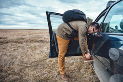 Hiker preparing footwear. Hiker standing by the car and tying  the shoelaces Royalty Free Stock Photography