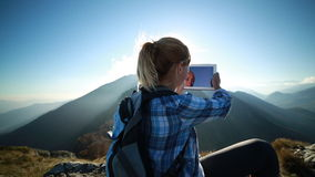 Hiker reaches mountain peak, takes picture of sunset stock video