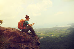 Hiker reading electronic book hiking on mountain peak. Successful woman hiker reading electronic book hiking on mountain peak Royalty Free Stock Photo