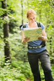 Hiker Reading a Map in a Forest Stock Photography