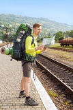 Hiker reading a map. Happy hiker man with backpack reading map at the train station. Traveler holding map, waiting for a train at train station and planing for Royalty Free Stock Image