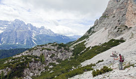 Hiker Reading Trail Signs. A hiker pauses to read the trail signs while backpacking through the Italian Dolomite Mountain Range Stock Photo