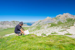 Hiker reading trekking map while resting at panoramic mountain spot. Outdoors activities, summer adventures and exploration on the Royalty Free Stock Photography