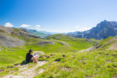 Hiker reading trekking map while resting at panoramic mountain spot. Outdoors activities, summer adventures and exploration on the Stock Photo