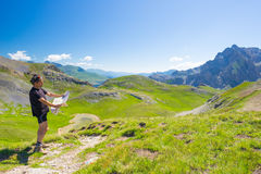 Hiker reading trekking map while resting at panoramic mountain spot. Outdoors activities, summer adventures and exploration on the Stock Photos