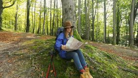 Hiker Reads Map. Joyful, beautiful female hiker reading a map as sitting near tall tree in wonderful, mountainous region on sunny morning stock footage