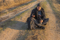 Hiker is ready to drink some tee sitting on rural road. Very tired hiker is ready to drink some tee sitting on rural road at autumnal evening Stock Photography