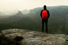 Hiker with red backpack on sharp sandstone rock in rock empires park and watching over the misty and foggy spring valley Stock Photos