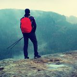 Hiker with red backpack on sharp sandstone rock in rock empires park and watching over the misty and foggy spring valley Royalty Free Stock Images