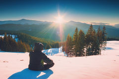 Hiker relaxing on a fresh snow and enjoy sunset Stock Image