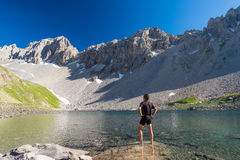 Hiker relaxing at high altitude blue lake in idyllic uncontaminated environment once covered by glaciers. Summer adventures and ex Stock Images