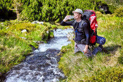 Hiker relaxing near mountain river and drinking bottled water Stock Images