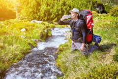 Hiker relaxing near mountain river and drinking bottled water Royalty Free Stock Photo