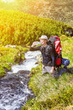 Hiker relaxing near mountain river and drinking bottled water Royalty Free Stock Photography