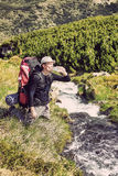 Hiker relaxing near mountain river and drinking bottled water Royalty Free Stock Photos