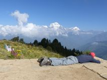 Hiker relaxing on Poon Hill, Dhaulagiri range, Nepal royalty free stock photography