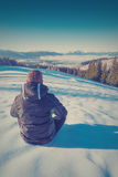 Hiker relaxing on a snow in a Carpathian mountain valley. Vintag Stock Photos