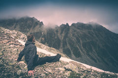 Hiker relaxing on top of a mountain. Instagram stylisation. Hiker relaxing on top of a mountain and enjoy dramatic sunset above the valley. Caucasian mountains Royalty Free Stock Photography