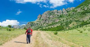 Hiker on the remote road to Valley of Ghosts in Crimean mountains. Lonely hiker on the remote road to Valley of Ghosts in Crimean mountains Royalty Free Stock Photo