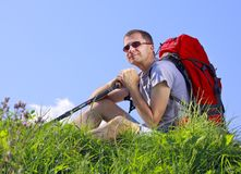 Hiker resting. Man hiker with trekking sticks and backpack sit on a grassy meadow Royalty Free Stock Images