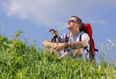Hiker resting. Man hiker with trekking sticks and backpack sit on a grassy meadow and looking up Stock Images