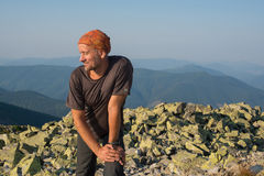 Hiker is resting on a background of mountains. Stock Photos