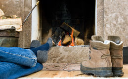 Hiker resting by the fireplace. Hiker warming up and relaxing by a small fireplace stock images