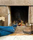 Hiker resting by the fireplace. Hiker warming uyp and relaxing by a small fireplace royalty free stock photography